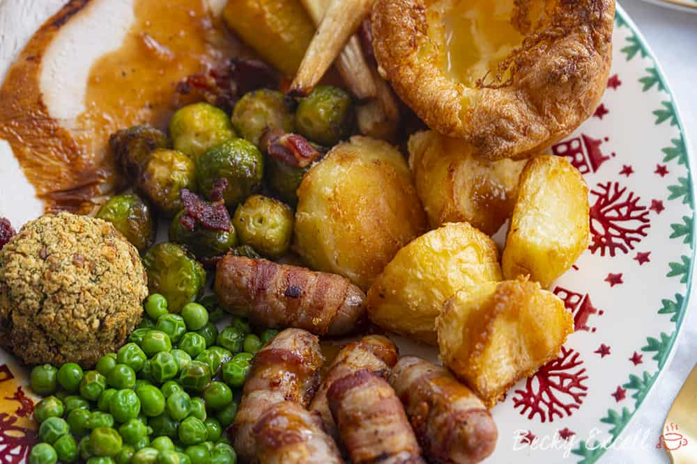 Gluten free roast dinner with roast potatoes, sprouts, pigs in blankets and roasted veg