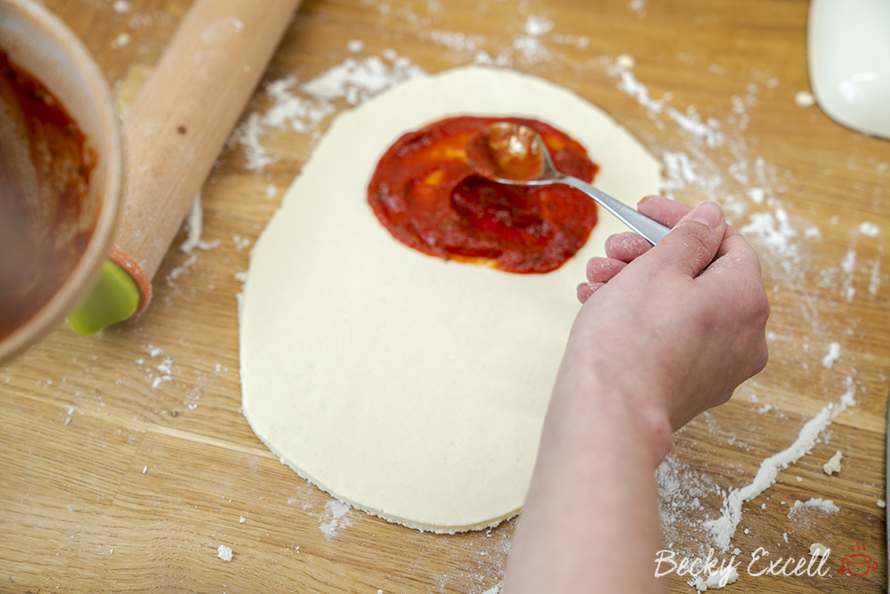 Time to add your homemade pizza sauce to the rolled out dough on one side