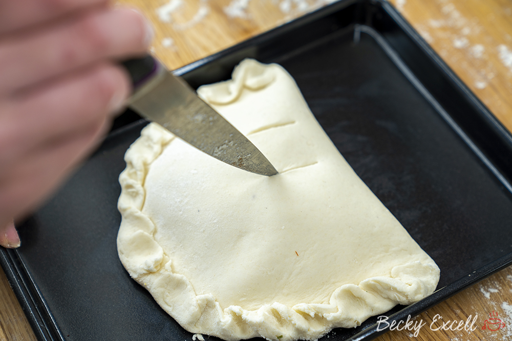 Using a sharp knife, cut three slits into the gluten free calzone so air can escape the dough